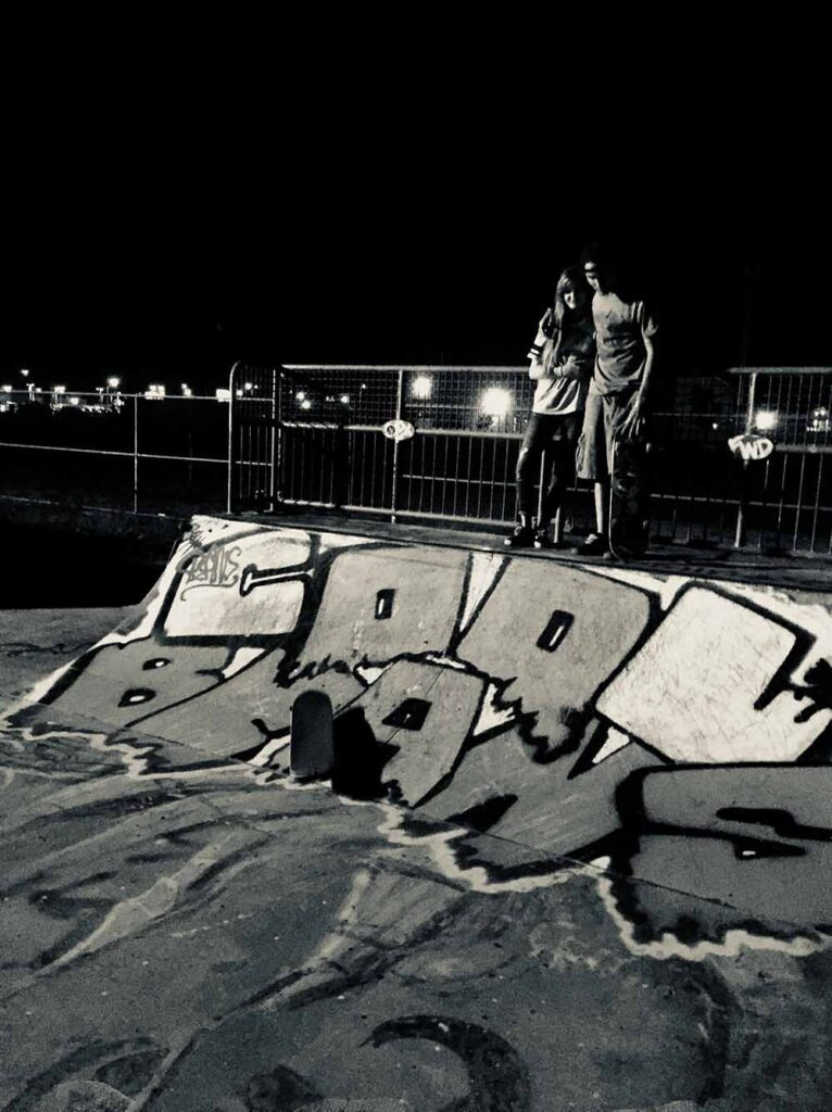 Boy and girl at the top of a short quarterpipe at night