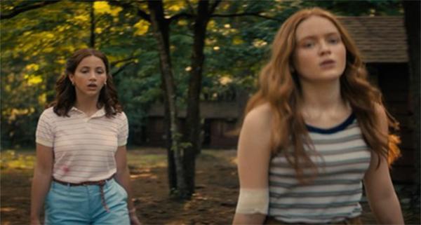 Two girls walking through woods