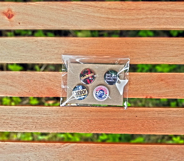badge set of four in a bag on a bench