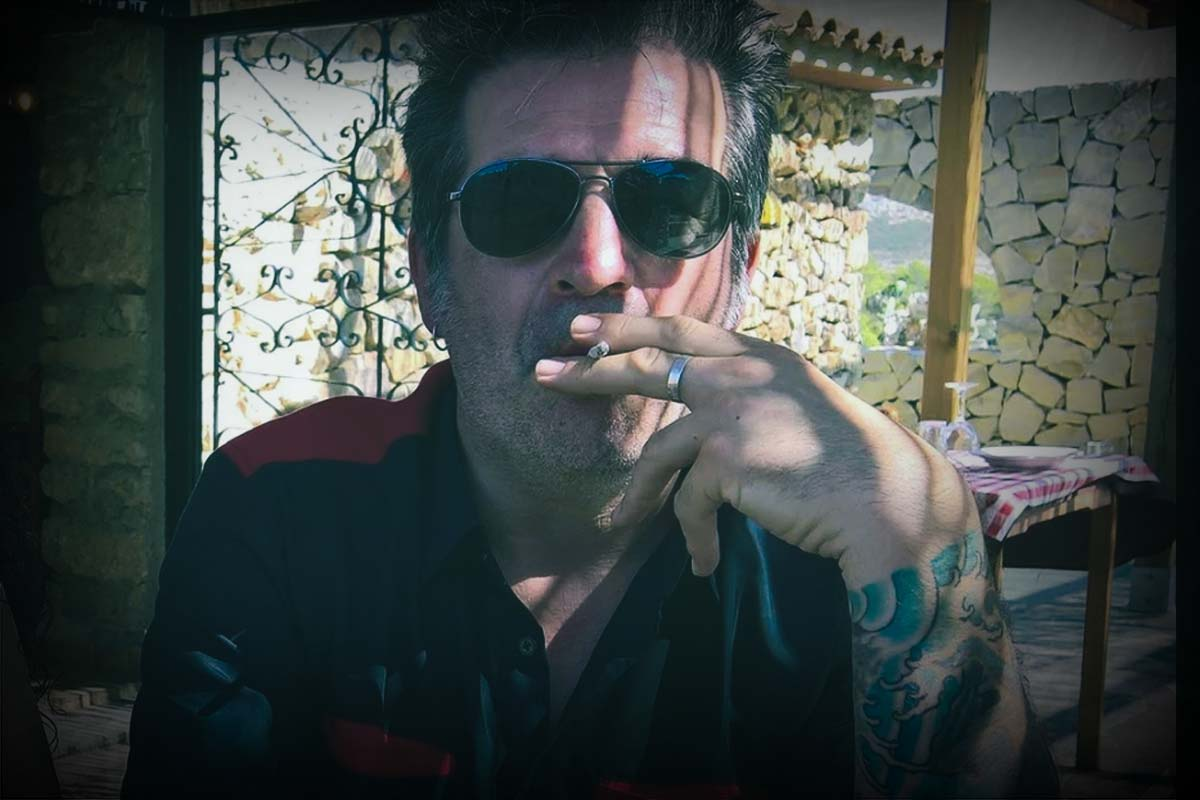Rich Deakin in sunglasses and smoking a cigarette